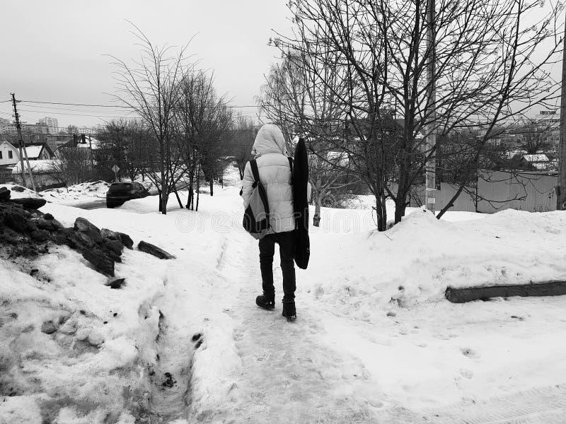 Молодой человек с гитарой идет весной или зима стоковая фотография rf