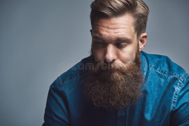 Молодой человек с длинной бородой глубоко в мысли стоковые фото