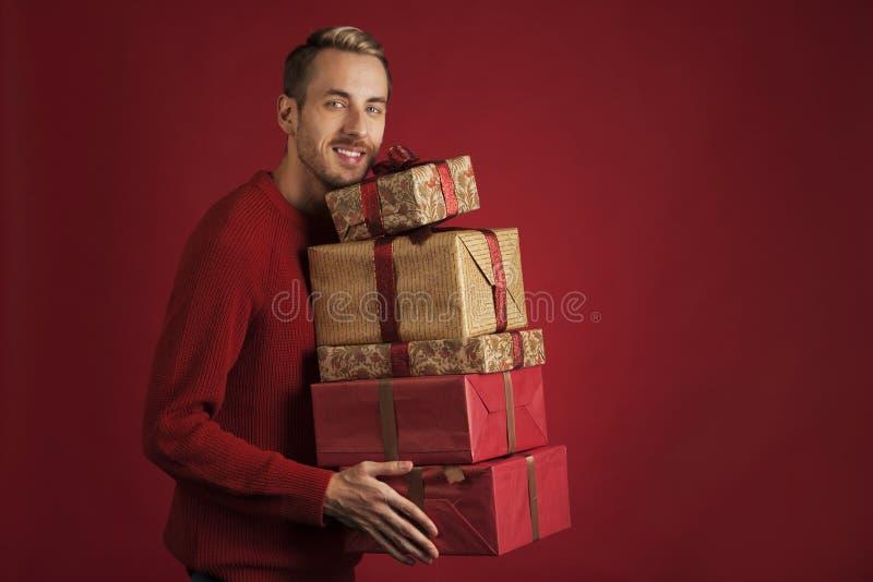 Молодой человек с коробками на красной предпосылке стоковое фото rf