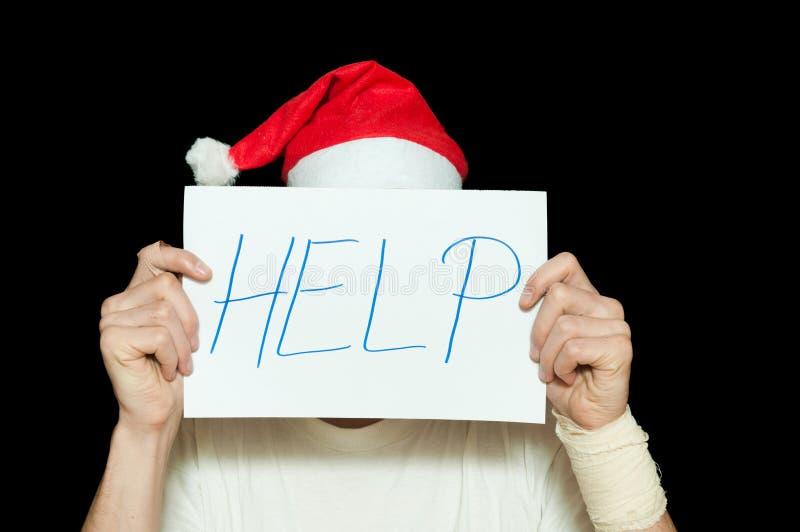Молодой человек с крышкой шляпы Санта Клауса его сторона с знаком помощи после суицидальной попытки чувствуя сиротливый и унылый  стоковые изображения