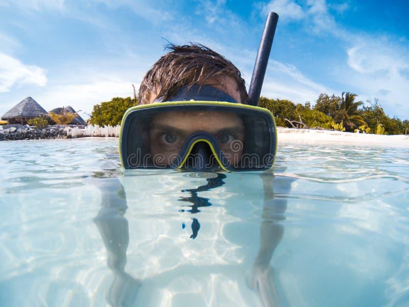 Молодой человек с маской акваланга в ясном открытом море смотря к камере стоковые фото