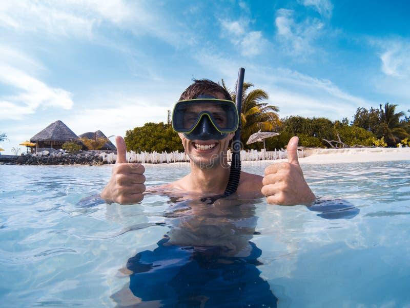 Молодой человек с маской акваланга усмехаясь к камере и показывая большой палец руки вверх стоковое фото rf