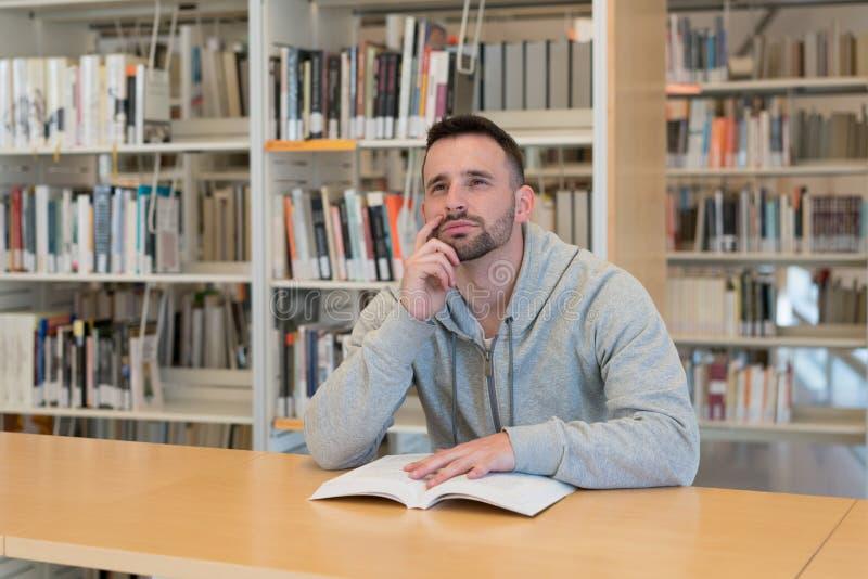 Молодой человек с пальцем на его стороне думая о возможных ответах с книгой на таблице в библиотеке стоковое изображение rf