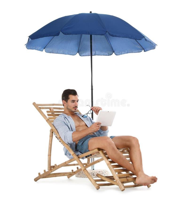 Молодой человек с планшетом на шезлонге под зонтиком против белой предпосылки стоковые фотографии rf