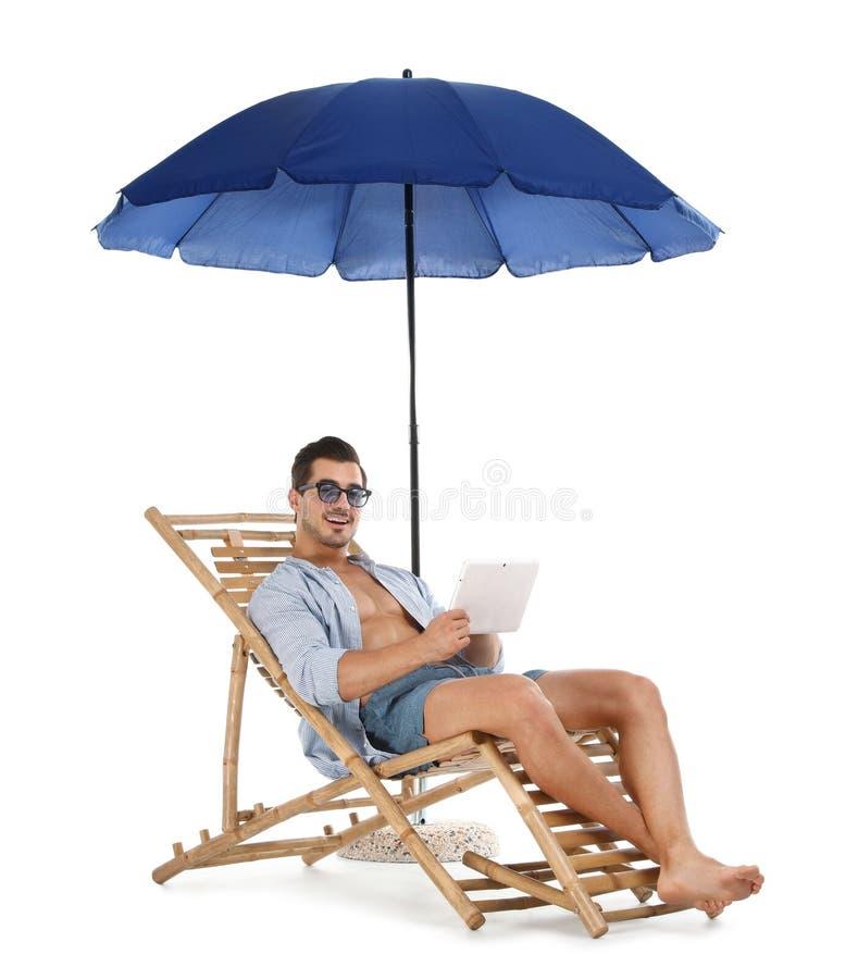 Молодой человек с планшетом на шезлонге под зонтиком против белой предпосылки E стоковое фото rf