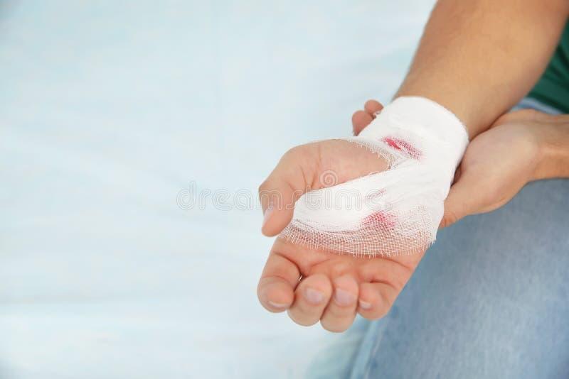 Молодой человек с повязкой на раненой руке в клинике, космосе для текста стоковые фото