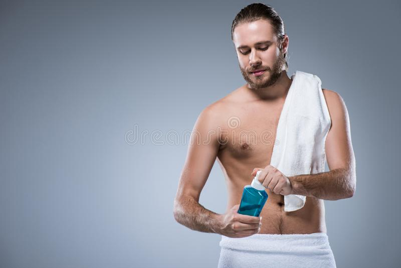 Молодой человек с полотенцем ванны на его плече держа бутылку с rinse зуба в руках, стоковые изображения