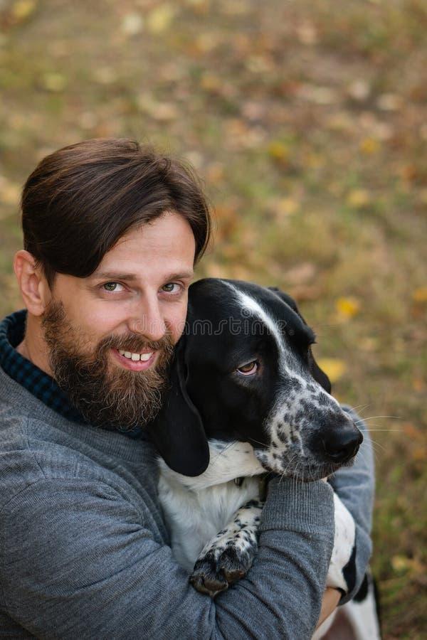 Молодой человек с прогулками собаки в парке осени Он обнял его любимца Собака охотящся, коротк-footed, сокращать-ушаста и пятнист стоковые изображения rf