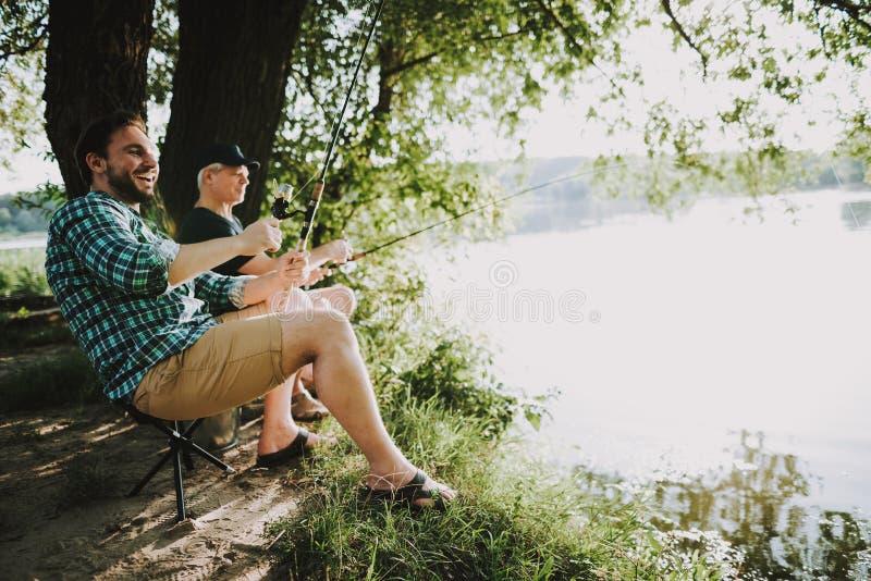 Молодой человек с рыбной ловлей сына и отца на реке стоковая фотография rf