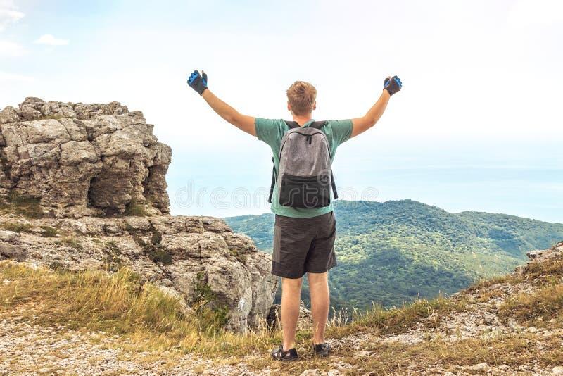 Молодой человек с рюкзаком поверх скалы наслаждаясь взглядом природы Горы и море стоковая фотография