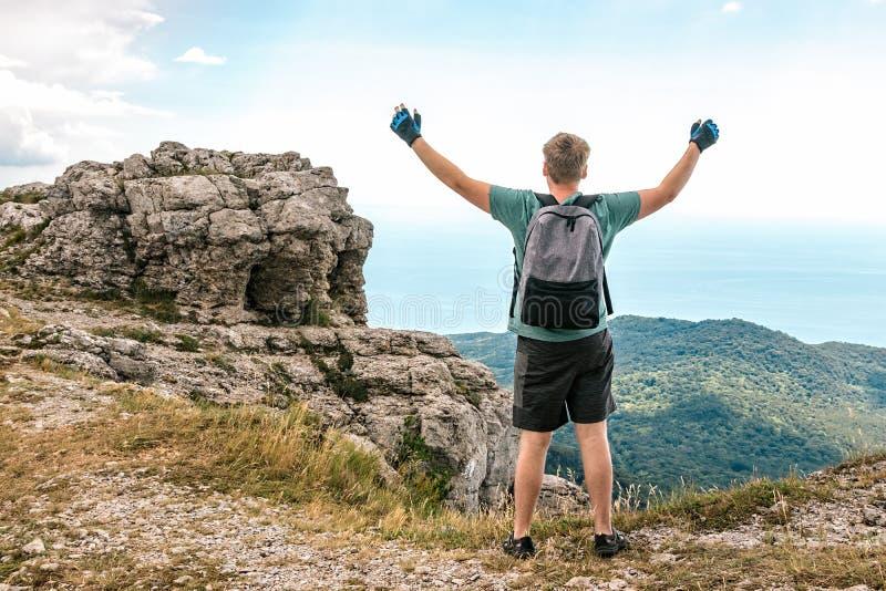 Молодой человек с рюкзаком поверх скалы наслаждаясь взглядом природы Горы и море стоковые изображения