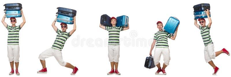 Молодой человек с тяжелыми чемоданами изолированными на белизне стоковая фотография