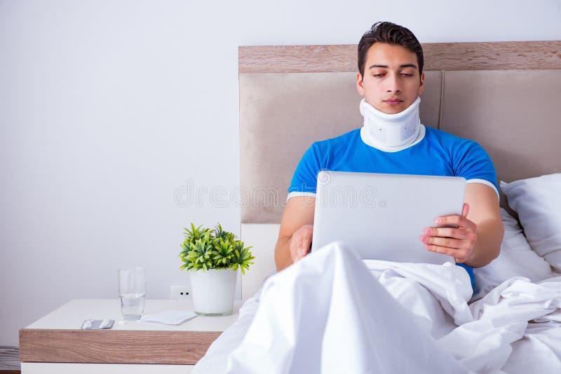 Молодой человек с ушибом шеи в кровати стоковая фотография rf