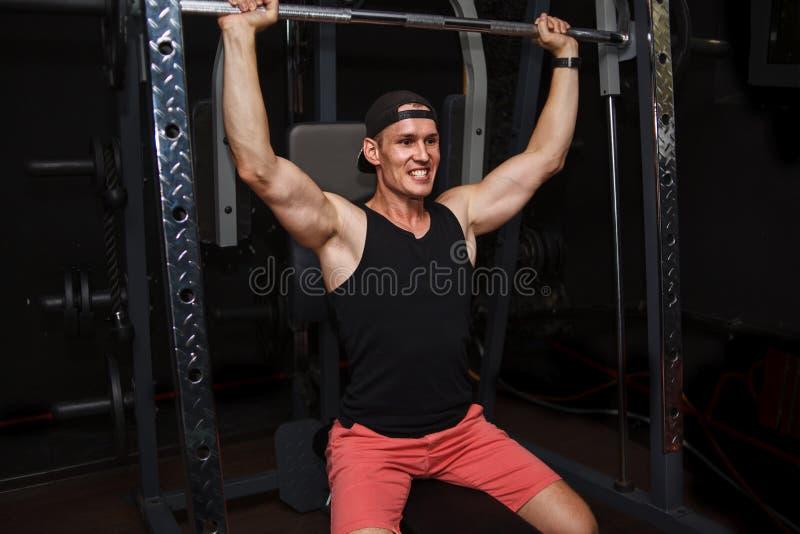Молодой человек тренирует его назад в спортзале стоковые изображения rf