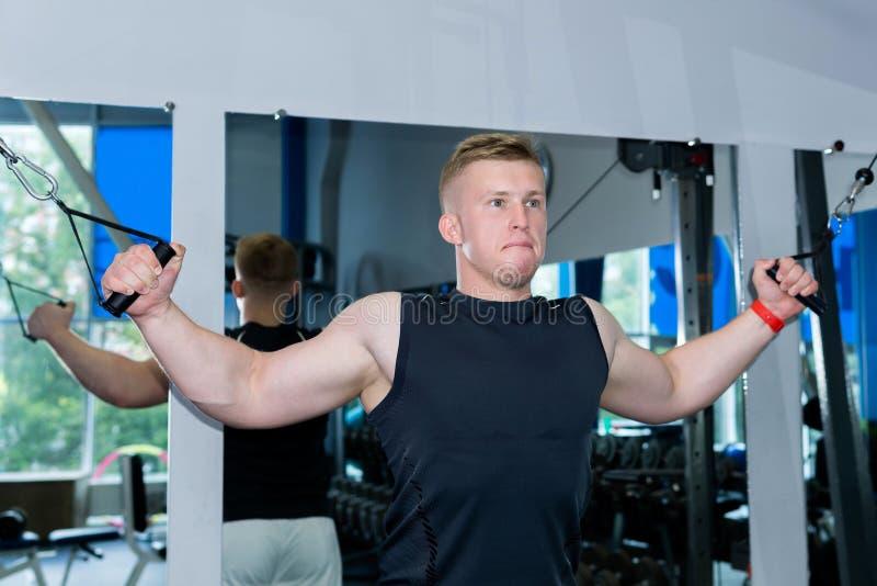 Молодой человек тренирует мышцы пояса плеча используя машину веса стоковые изображения rf