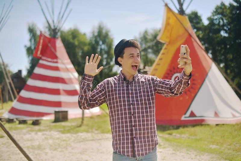 Молодой человек туристский принимает selfie/видеосвязь и усмехаться фото на доме teepee/типи предпосылки родном индийском человек стоковое фото
