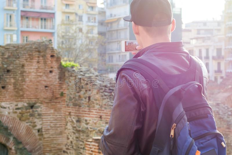 Молодой человек, турист, с рюкзаком, изображение на смартфоне дворец Galerius на заходе солнца стоковое изображение rf