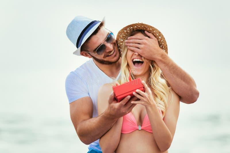 Молодой человек удивительно его подруга с подарком на пляже стоковое фото