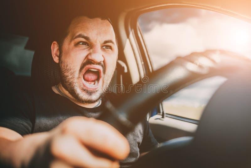 Молодой человек управляя автомобилем в клекотах удара в страхе за аварию стоковое изображение rf