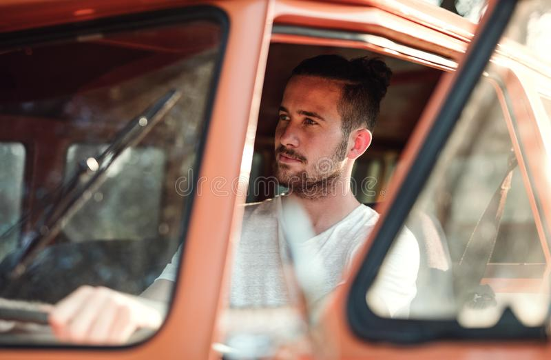 Молодой человек управляя автомобилем на roadtrip через сельскую местность стоковое изображение