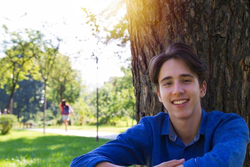 Молодой человек усмехаясь и сидя на траве около дерева на парке стоковая фотография