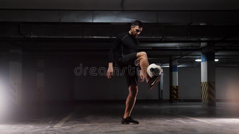 Молодой человек футбола тренируя основные фокусы с шариком балансируя шарик на поднятых ногах стоковая фотография rf