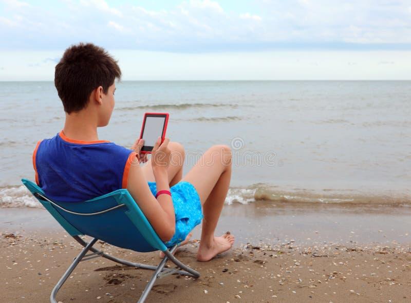 Молодой человек читает книгу на пляже стоковое изображение rf