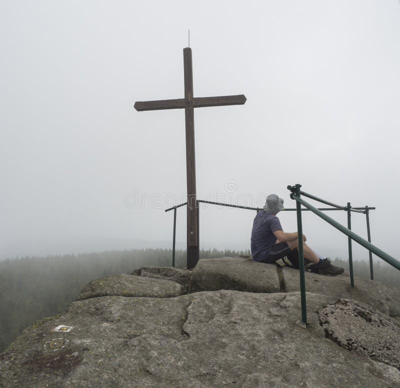Молодой человек hiker сидя на верхнем пике утеса горы Jizera стоковая фотография