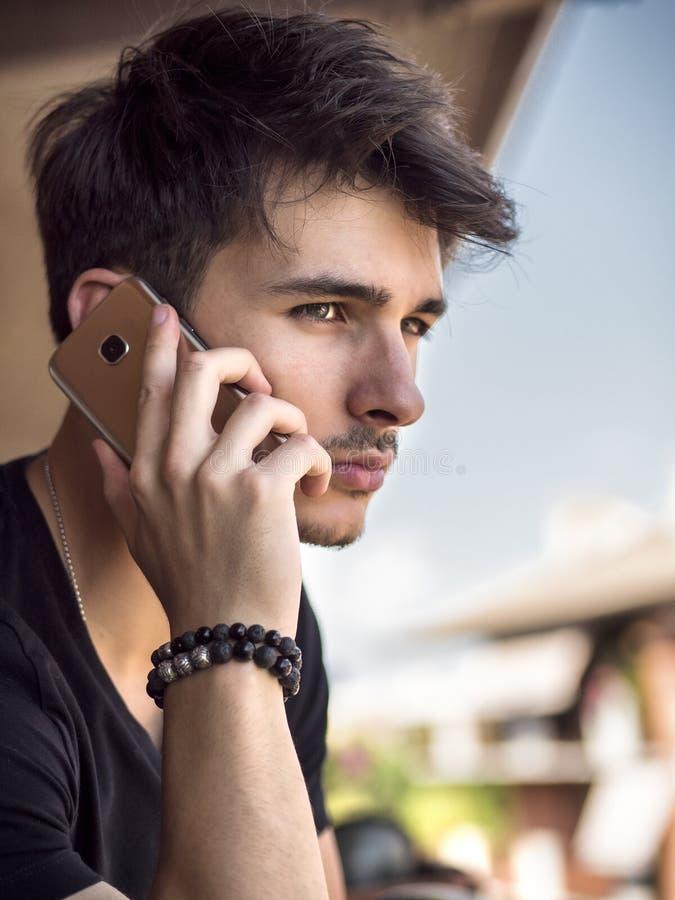 Молодой человек outdoors говоря на сотовом телефоне стоковое изображение
