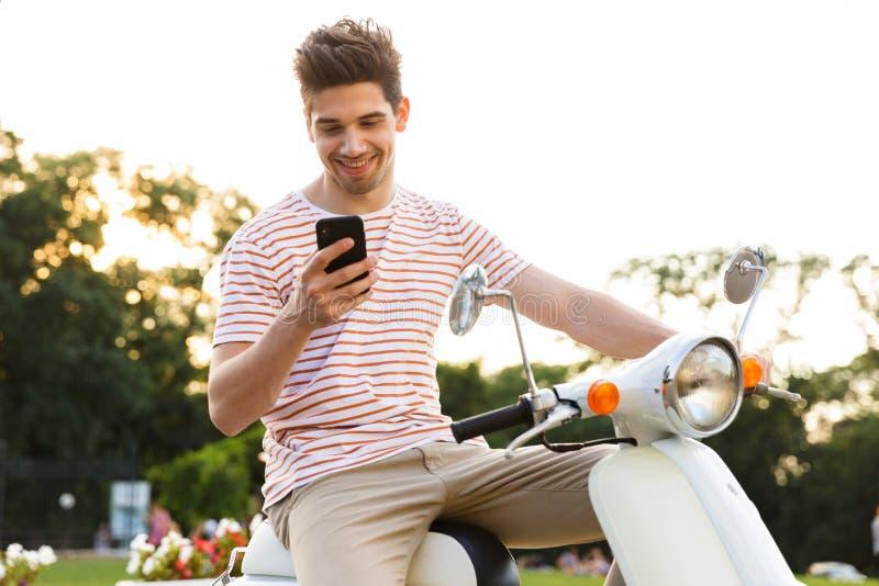Молодой человек 20s сидя на мотоцикле в улице города и держа мобильный телефон стоковое фото rf