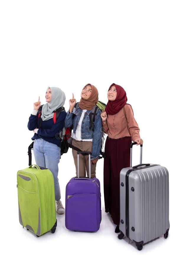 Молодой чемодан удерживания положения женщины hijab, сумка с указывать рук стоковые фотографии rf
