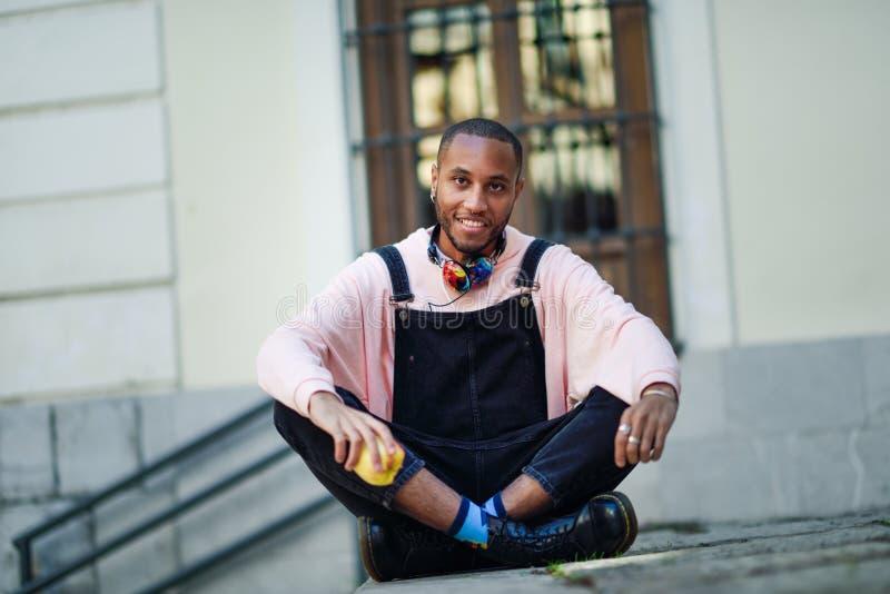 Молодой чернокожий человек есть яблоко сидя на городских шагах стоковые изображения