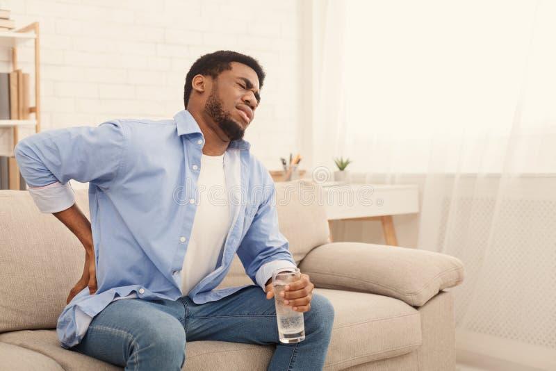 Молодой чернокожий человек с болью в спине дома стоковые изображения rf