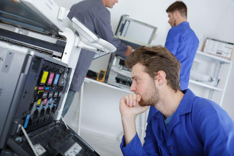 Молодой эффективный инженер работая на принтере и регулируя компоненты стоковое изображение