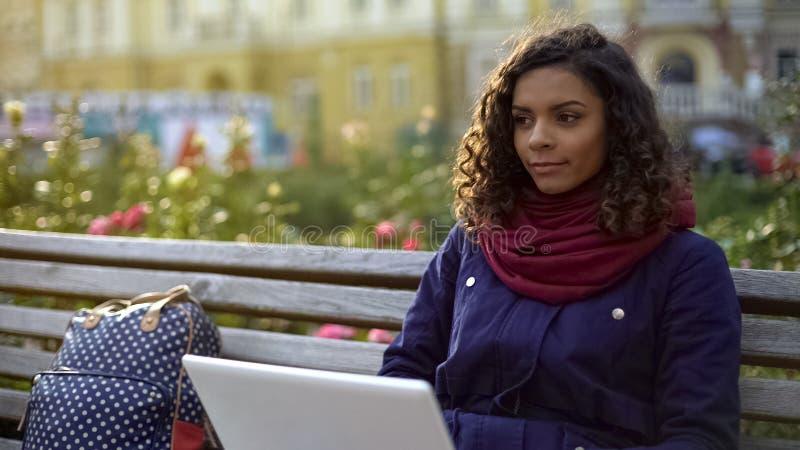 Молодой biracial писатель работая на новом проекте, сидя с компьтер-книжкой outdoors стоковая фотография