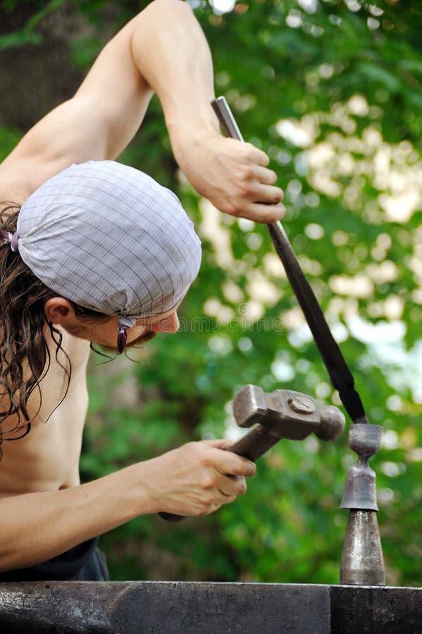 Молодой blacksmith горячий утюг молотком стоковые фотографии rf