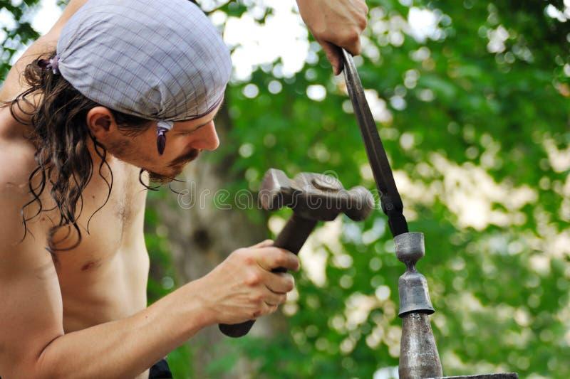 Молодой blacksmith горячий утюг молотком стоковые изображения