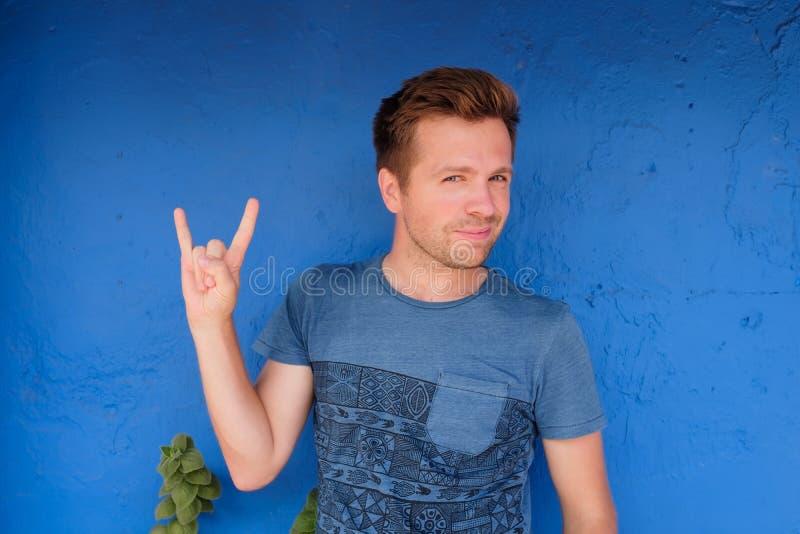 Молодой excited кавказский человек в голубой футболке, показывая рожкам жест рукой с одним рукой и усмехаться стоковые фотографии rf