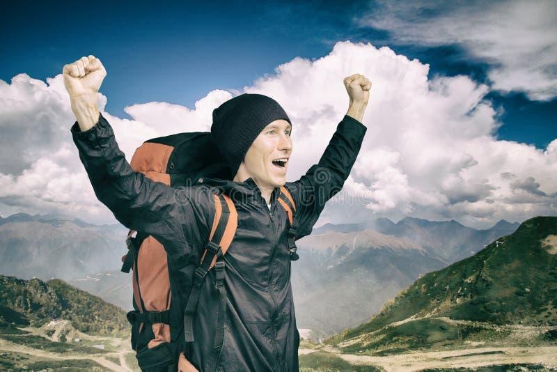 Молодой hiker крича вне на верхней части с его руками поднял, взгляд со стороны стоковое изображение