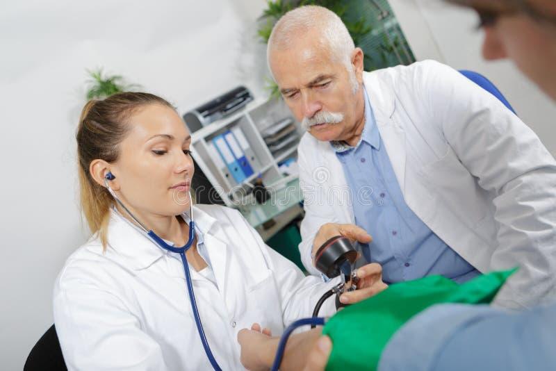Молодой internist принимая пациентам кровяное давление с coleague стоковые изображения rf