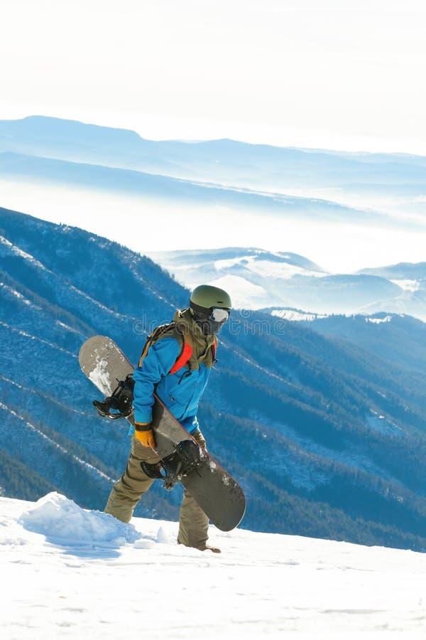 Молодой snowboarder идя вверху гора с сноубордом в его руке стоковое фото