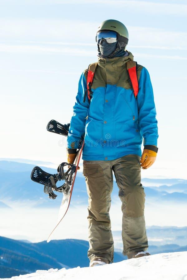 Молодой snowboarder стоя вверху гора и держа его сноуборд с одной рукой стоковые фотографии rf