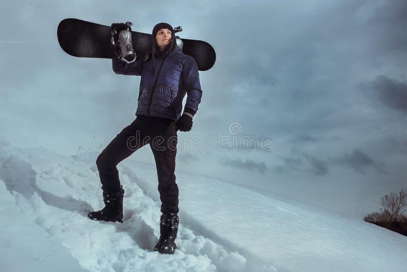Молодой snowboarder стоя на холме и держа доску для сноубординга стоковые фотографии rf