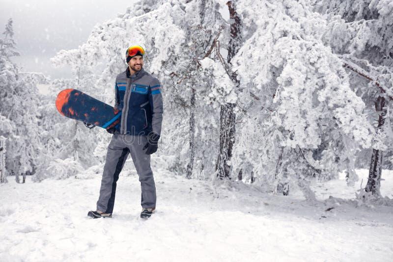 Молодой snowboarder с сноубордом на зимнем отдыхе в mounta стоковые фотографии rf