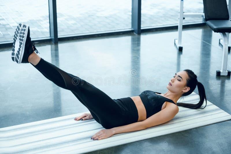 молодой sporty делать женщины V-поднимает на циновке йоги стоковые изображения rf