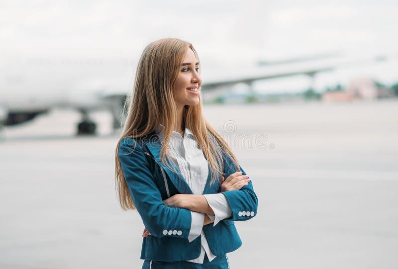 Молодой stewardess в форме на автостоянке воздушных судн стоковое изображение
