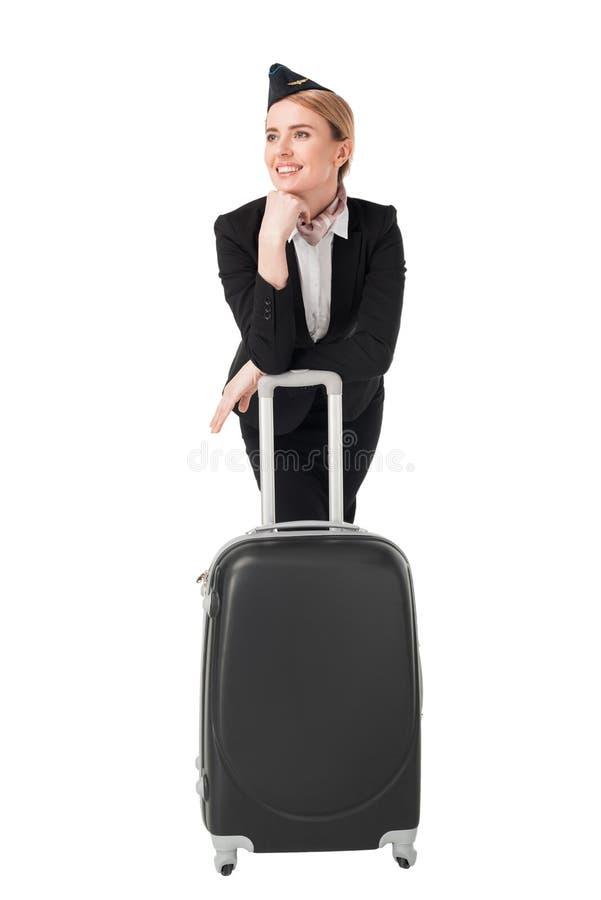 Молодой stewardess в форме полагаясь на чемодане стоковое фото rf