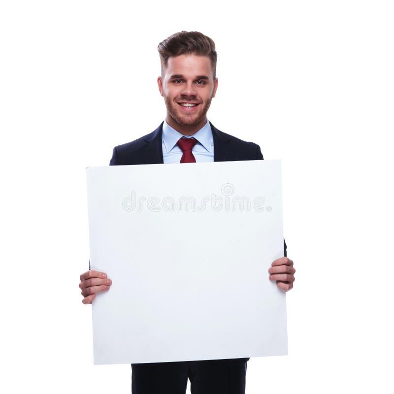 Молодой unshaved бизнесмен держит пустую афишу стоковые изображения rf