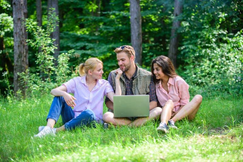 Молодость компании тратит отдых outdoors с компьтер-книжкой Друзья работая с компьтер-книжкой на зеленом луге Современные техноло стоковое фото rf