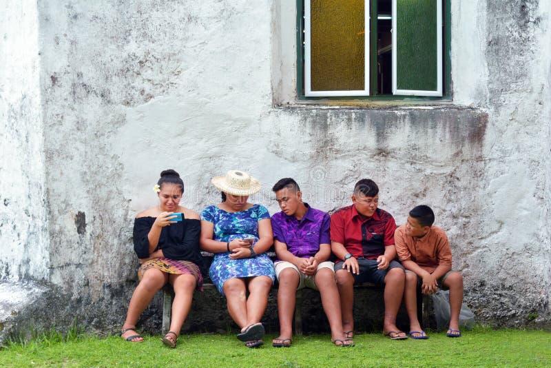 Молодость островитянин кашевара висит вне внешнюю церковь Raroton Avarua CICC стоковое изображение rf